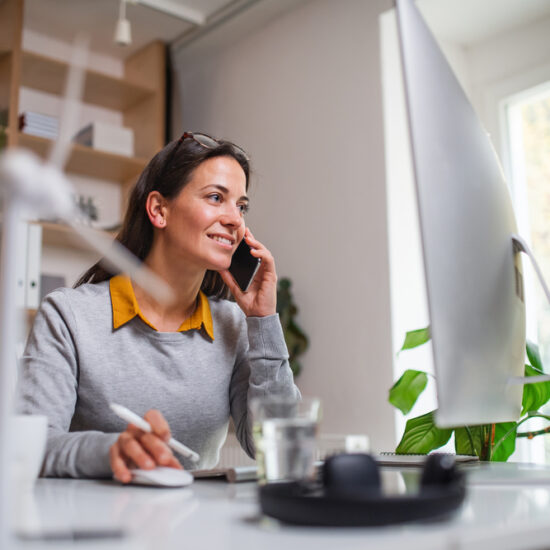 Woman Using Phone and Computer